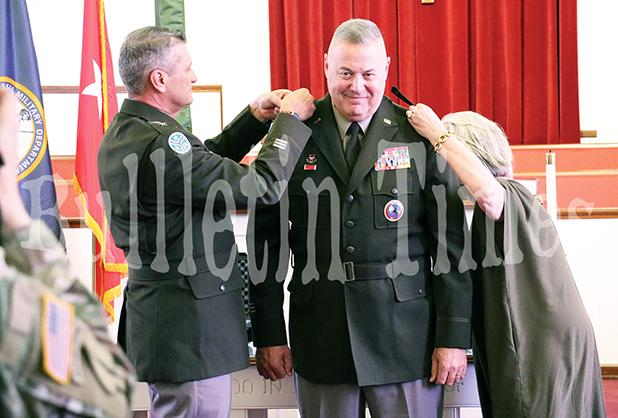 Tennessee Adjutant General Major General Jeff Holmes and wife Becky Ross pin the hardware on Ross during the ceremony.