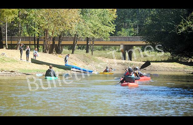 A group of canoers and kayakers approach Charles T. Russell Landing and Hatchie Town River Park.
