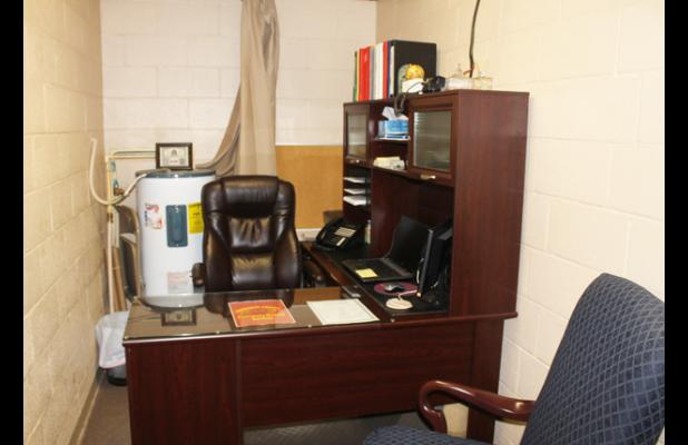 The director's office, a closet converted to an office, narrowly holds two individuals and is highlighted with the hot water heater placed behind the director.