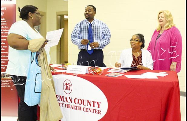 Robert Davis, Jr., Cassandra Bufford, and CEO Mary Heinzen from the Hardeman County Community Health Center talk with a patron. Photo by Ginger Tester.