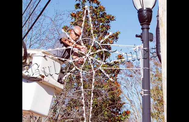 Ricky Galloway operates from the bucket truck to secure Christmas stars and snowflakes in Bolivar.