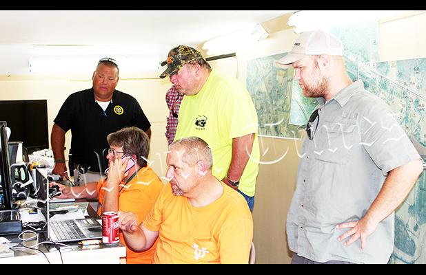 Sheriff Doolen and members of the search team watch live drone footage scanning the area. Photo by Jessica Simmons