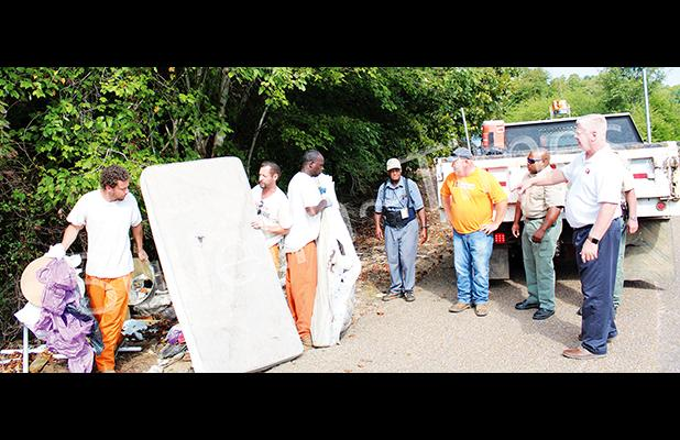 Trustees from the Sheriff's Department, Sheriff's Deputies, Hardeman County Solid Waste Director Kenny Brown and Mayor Sain pitch in to clean up an illegal dumping site on Hannis Road on September 9.