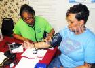 Cassandra Bufford, a RN at the Hardeman County Community Health Center takes Nikita Dennis' blood pressure during the mini health fair at Greater Victory Church on Saturday, March 12.