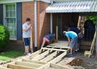 Youth work with adults at Y.E.P. to build wheelchair ramps at two homes for individuals in need of a ramp.