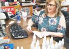 The Vaughan Oil Company is donating hand sanitizer to first responders in Hardeman County, using suppliers from the State of Tennessee to do the job. Photo: Volunteer Janna Vaughan labels the bottles.