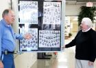 James Kirk, Vice President of CAB, and Mitch Carter of Moore's Studio are shown discussing the completed Full-Vue Wall Display of Middleton High School senior composites displayed in the school lobby.